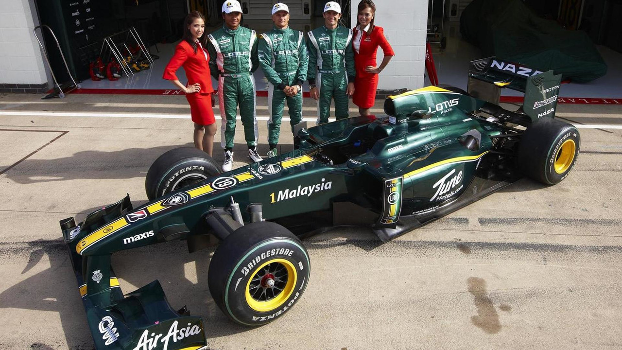 Lotus drivers pose by F1 car