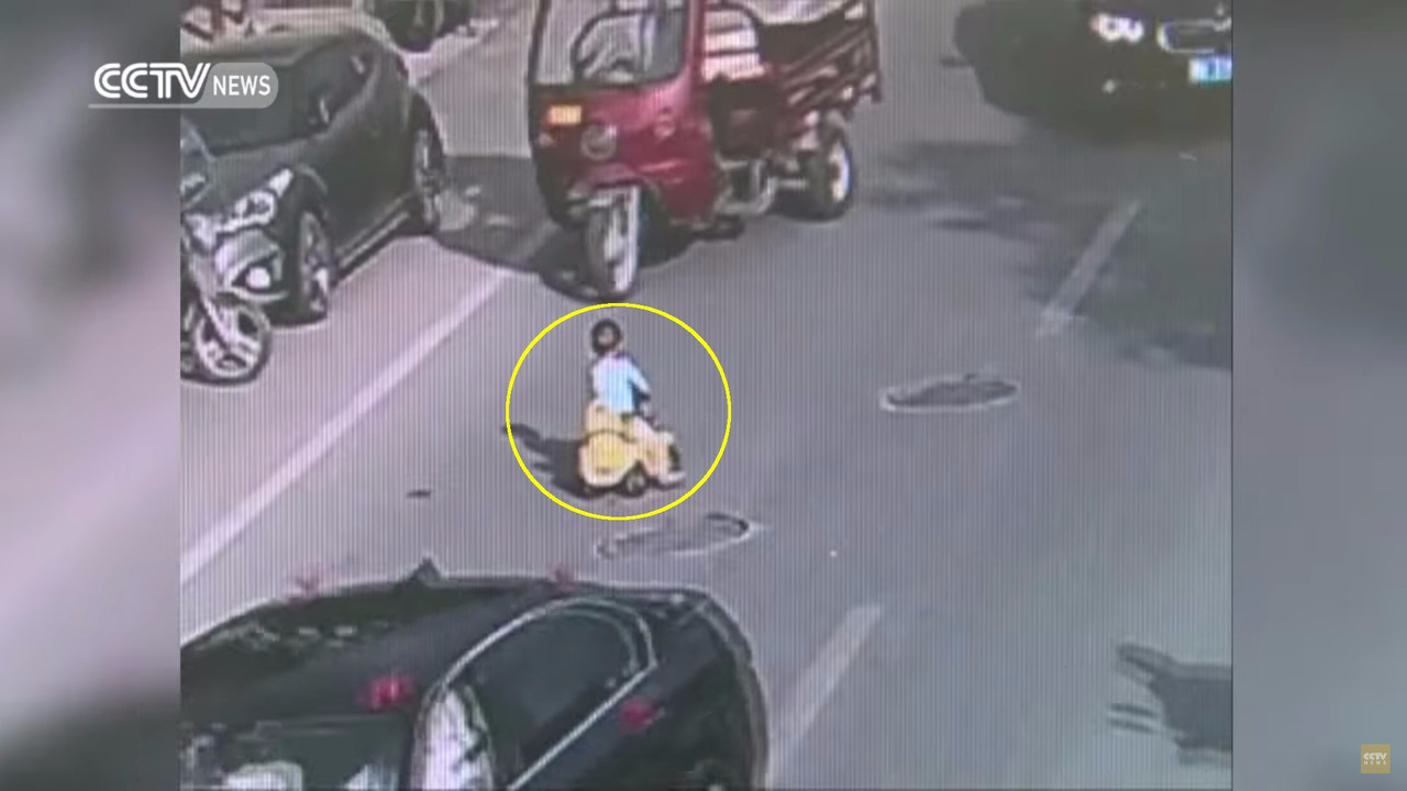 Toddler rides toy car on highway