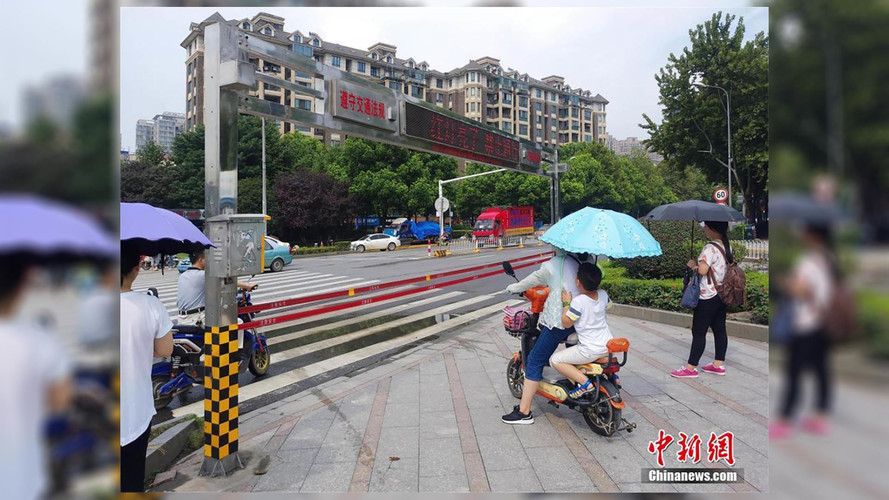 Kötelekkel próbálják megállítani a zebránál türelmetlenkedő kínai embereket