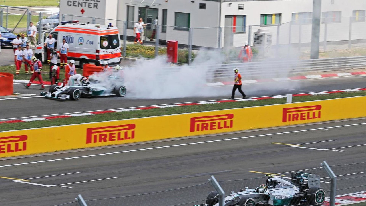 Nico Rosberg (GER) passes team mate Lewis Hamilton (GBR), who stopped in the pitlane during qualifying after suffering a fire, 26.07.2014, Hungarian Grand Prix, Budapest / XPB